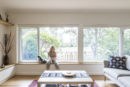 A woman sitting in front of large windows in her home. When renovating or retrofitting ventilation is an important point to consider.