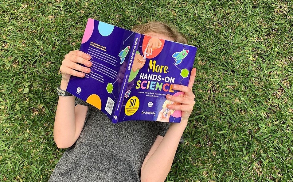 child laying on grass reading hands on science book