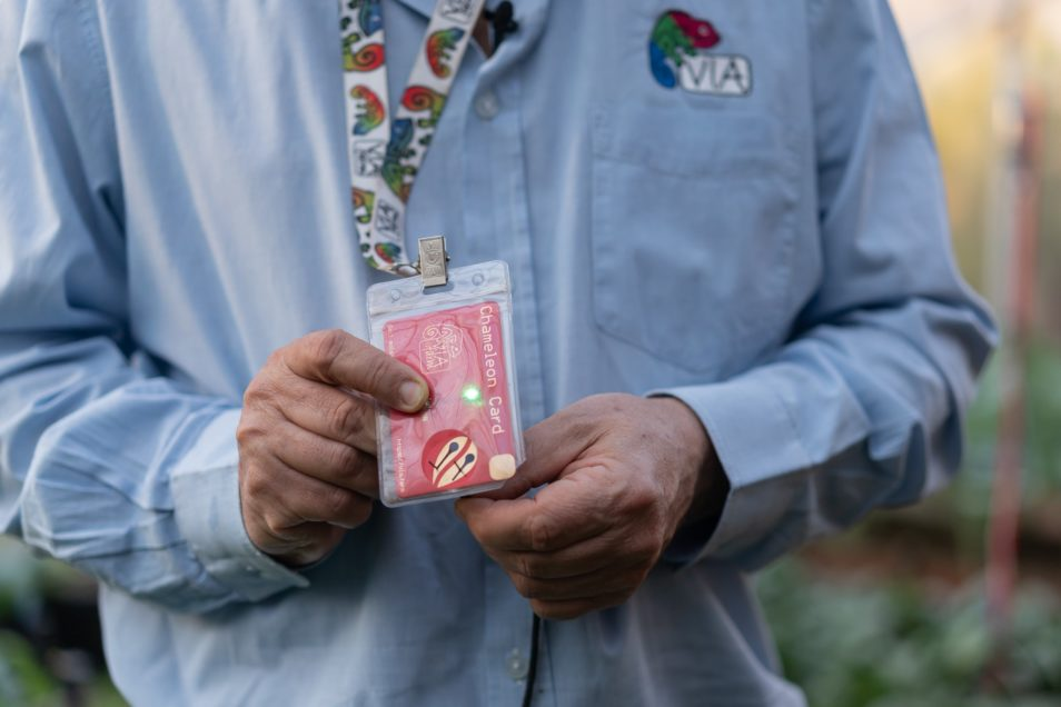 A red Chameleon Card worn on a lanyard around a man's neck