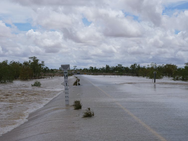 A flooded road in Northern Territory with a flood marker.