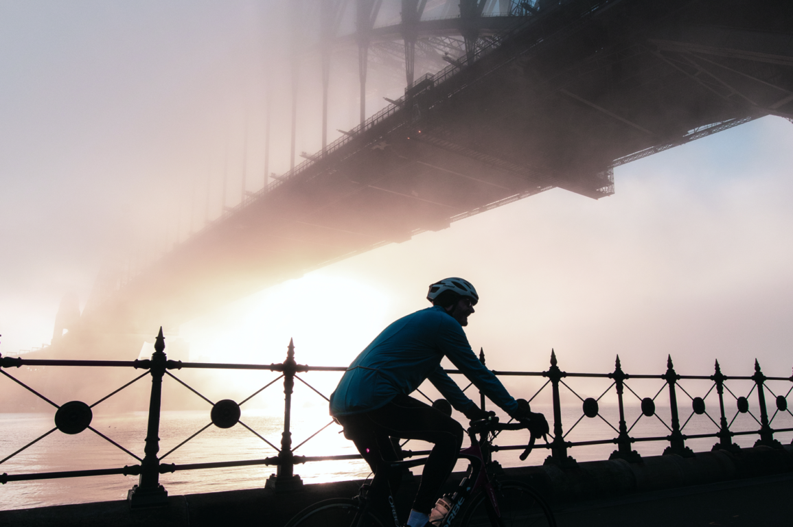 Man riding bike under the Sydney Harbour Bridge