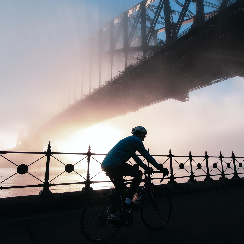 Man riding bike under the Sydney Harbour Bridge