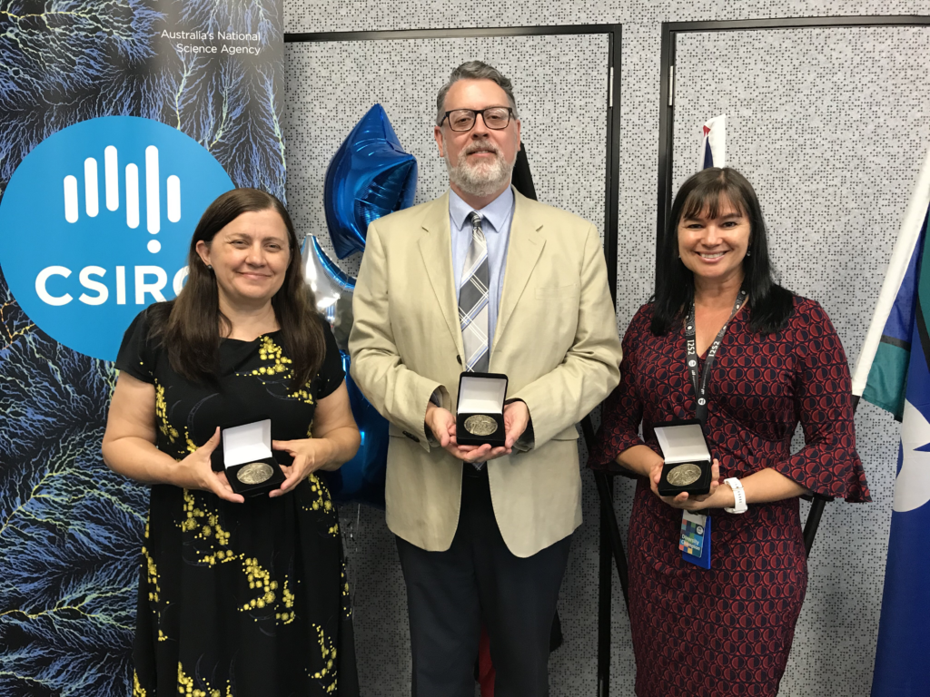 Three members of the Indigenous STEM Education Project team: Dr Jen Parsons, Dr Chris Banks and Kim Dyball holding their CSIRO Awards medals.