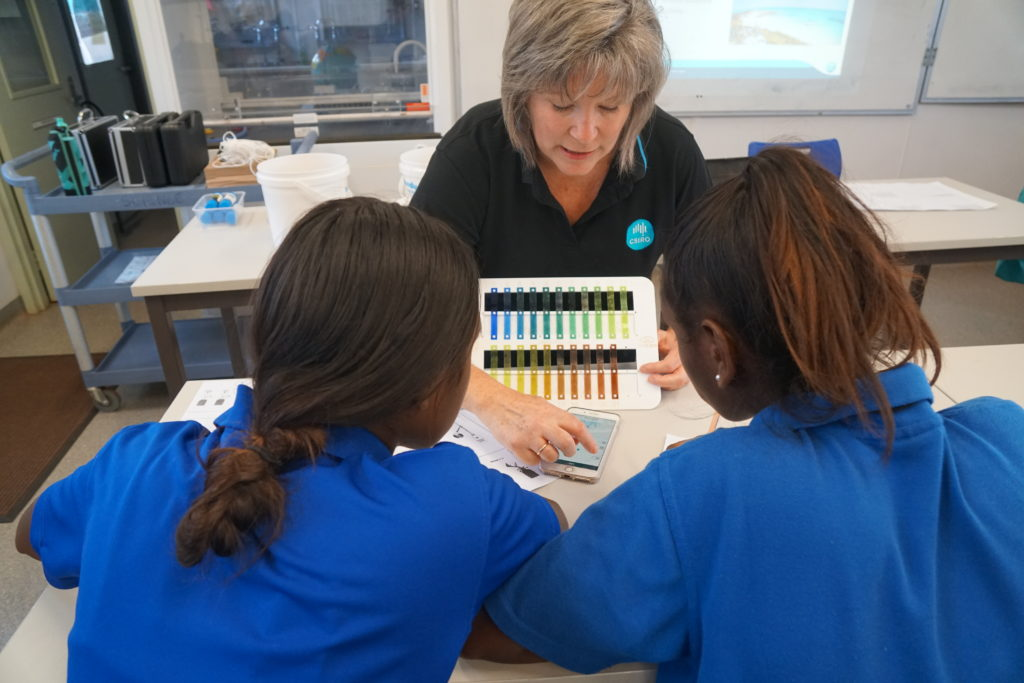 Woman showing the Eye On Water app to two students