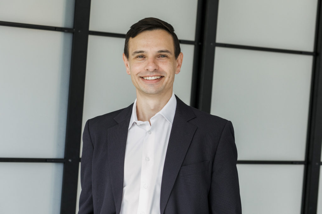 A male expert in commercialising innovation in a suit smiling at the camera