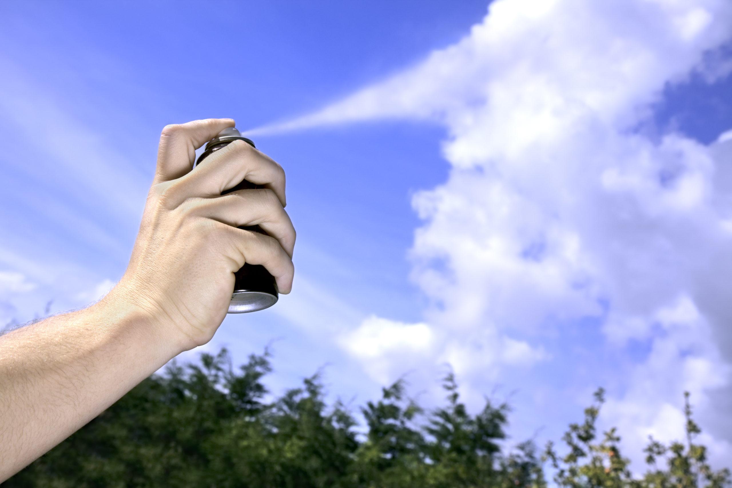 A person spraying aerosol into the air.