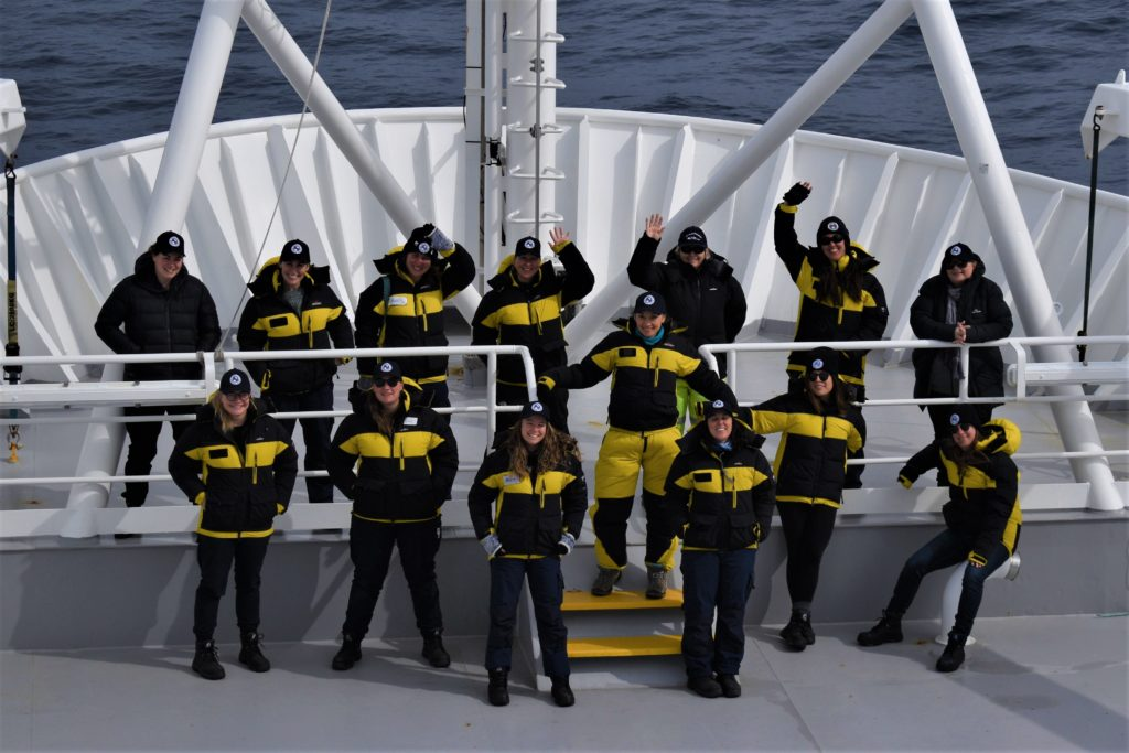 14 women in cold weather gear on a ship