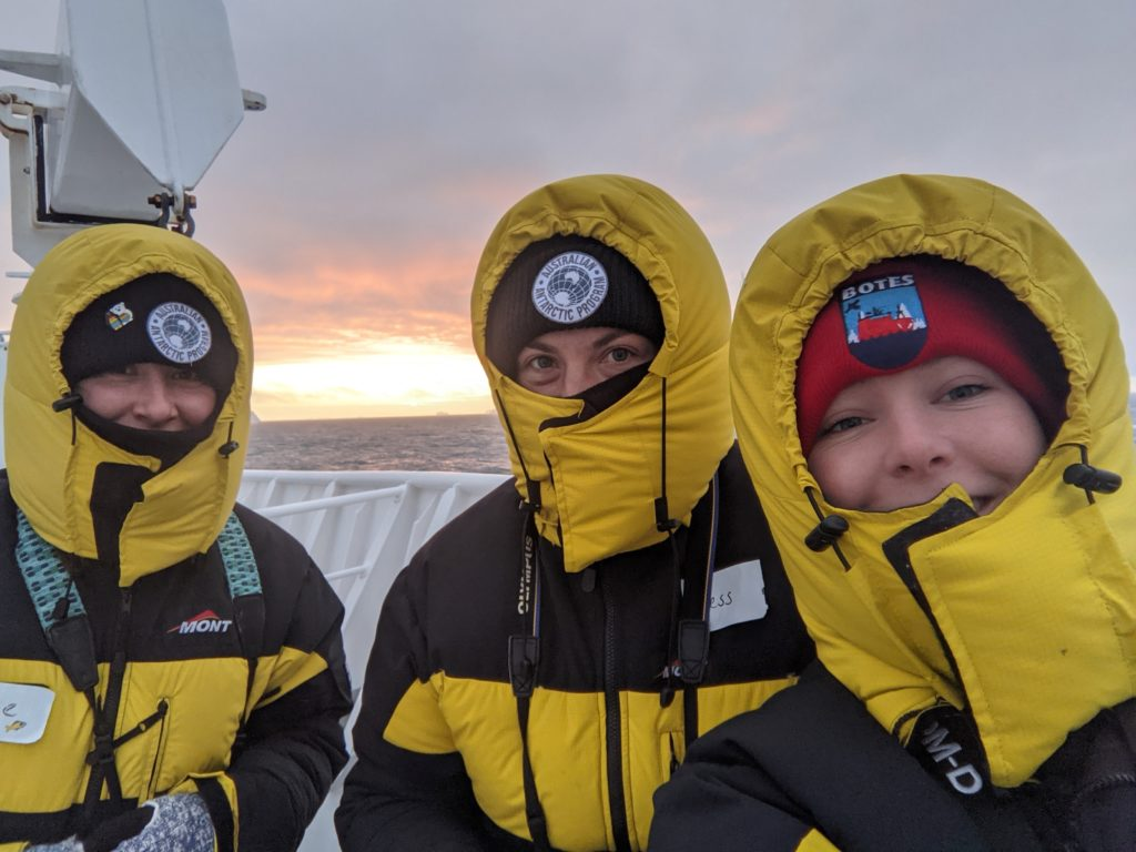 Three women in cold weather gear on a ship