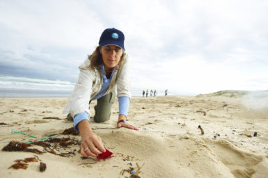Denise Hardesty on her hands at the beach reaching for plastic