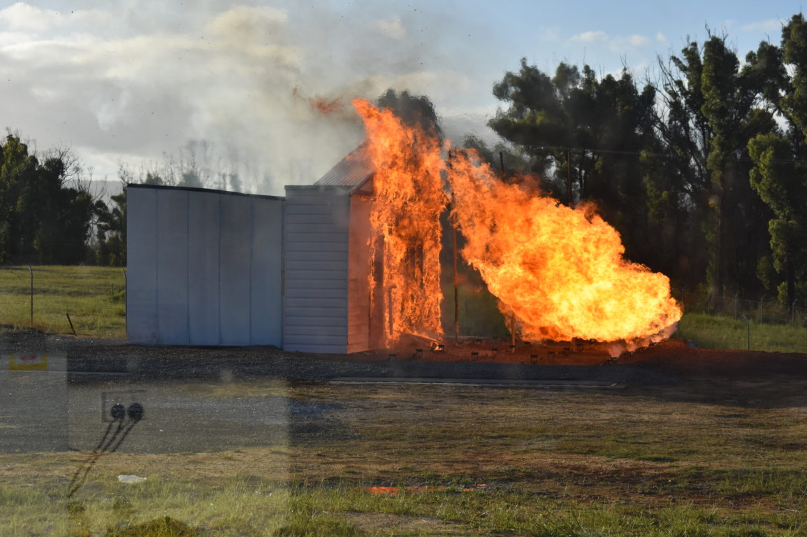 Image of a burnover experiment conducted by Justin Leonard where the house is beginning to ignite.