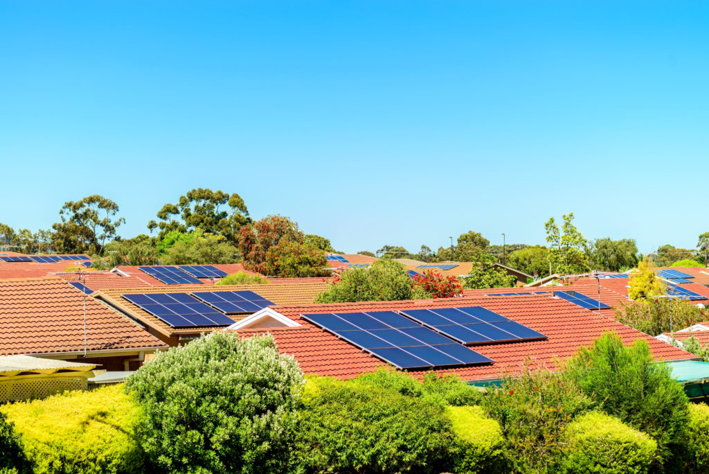 Suburban house roofs featuring solar PV installation.