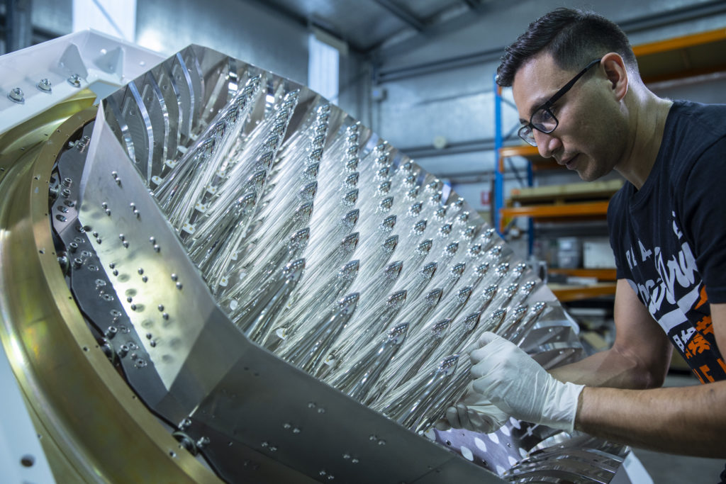 A person leans over a hexagon shaped instrument tilted toward them. The hexagon contains many silver metallic rocket-shaped elements pointing toward the person. This technology will be used by Quasar Satellite Technologies.