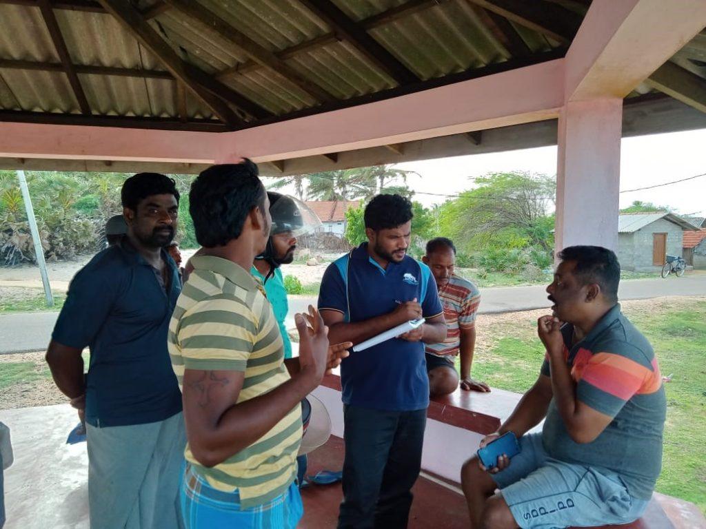 Group of six men talking with Lahiru