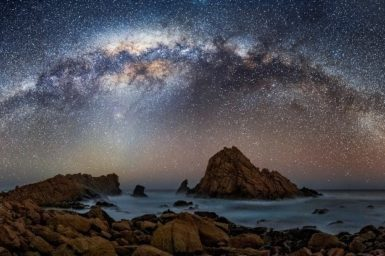 A astrophotograph of stars in the nights sky with an ocean in the foreground at night time.