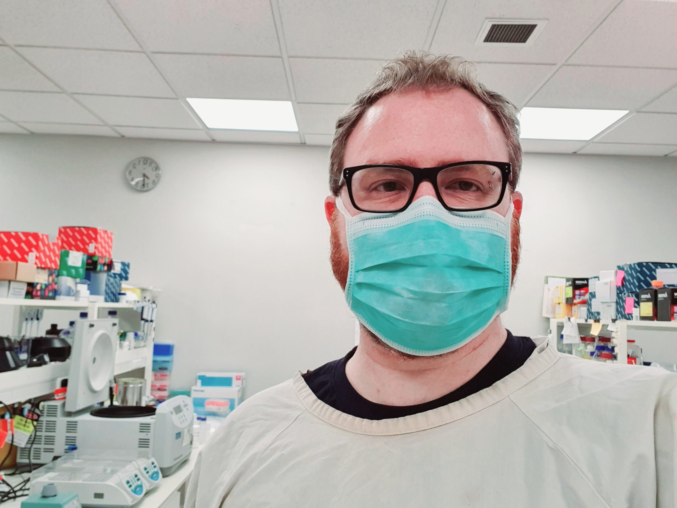 A man in a surgical mask and lab gear.