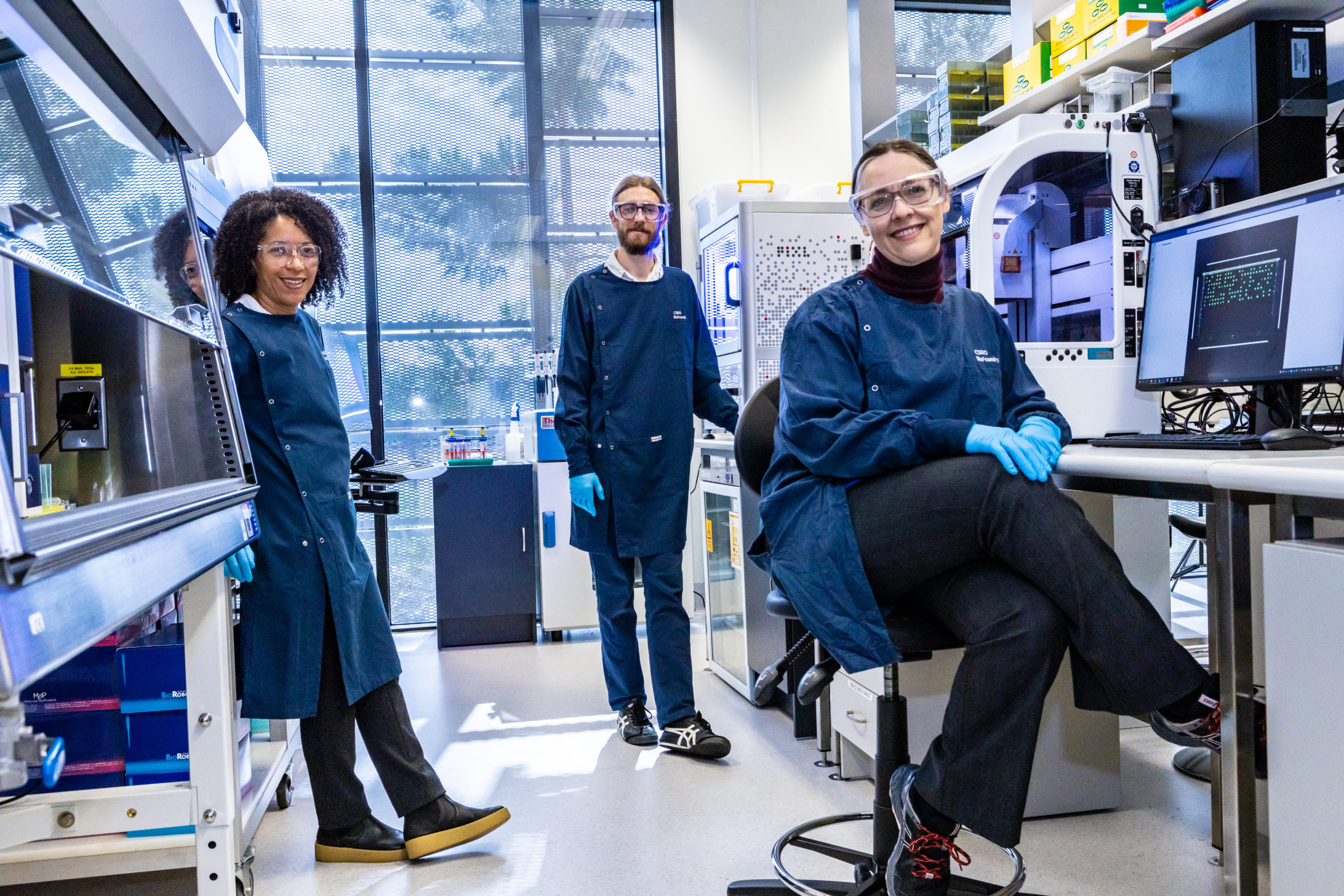 Synthetic biology team in lab gear smiling at camera