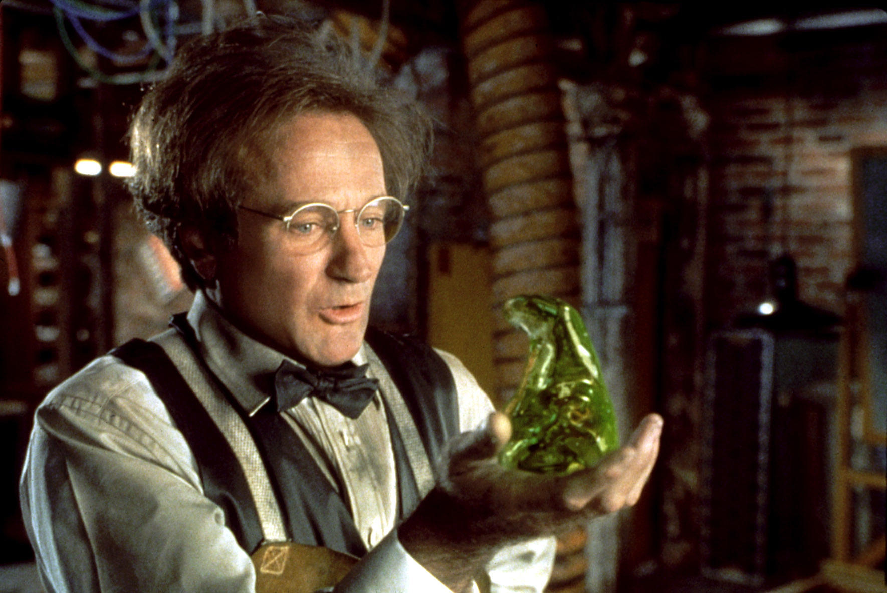 Man in glasses holding flubber - a green stretchy blob