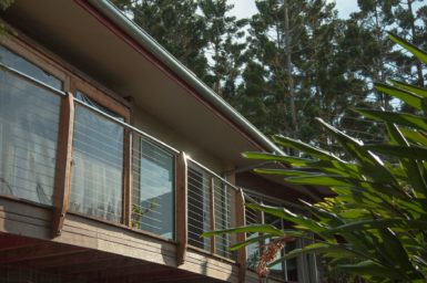 A picture looking up at the shaded veranda of a sustainable Australian home, surrounded by vegetation