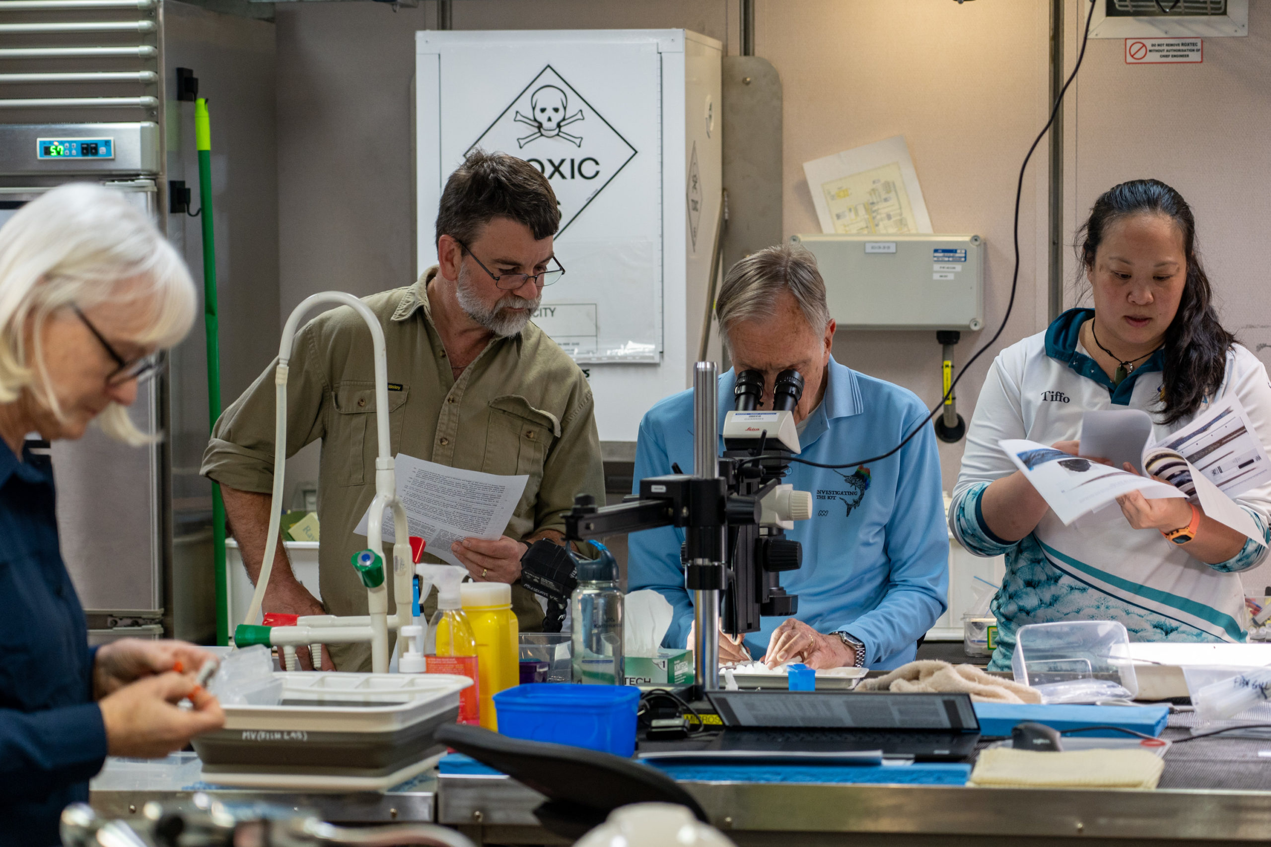 Scientists looking at deepwater creatures with their equipment.