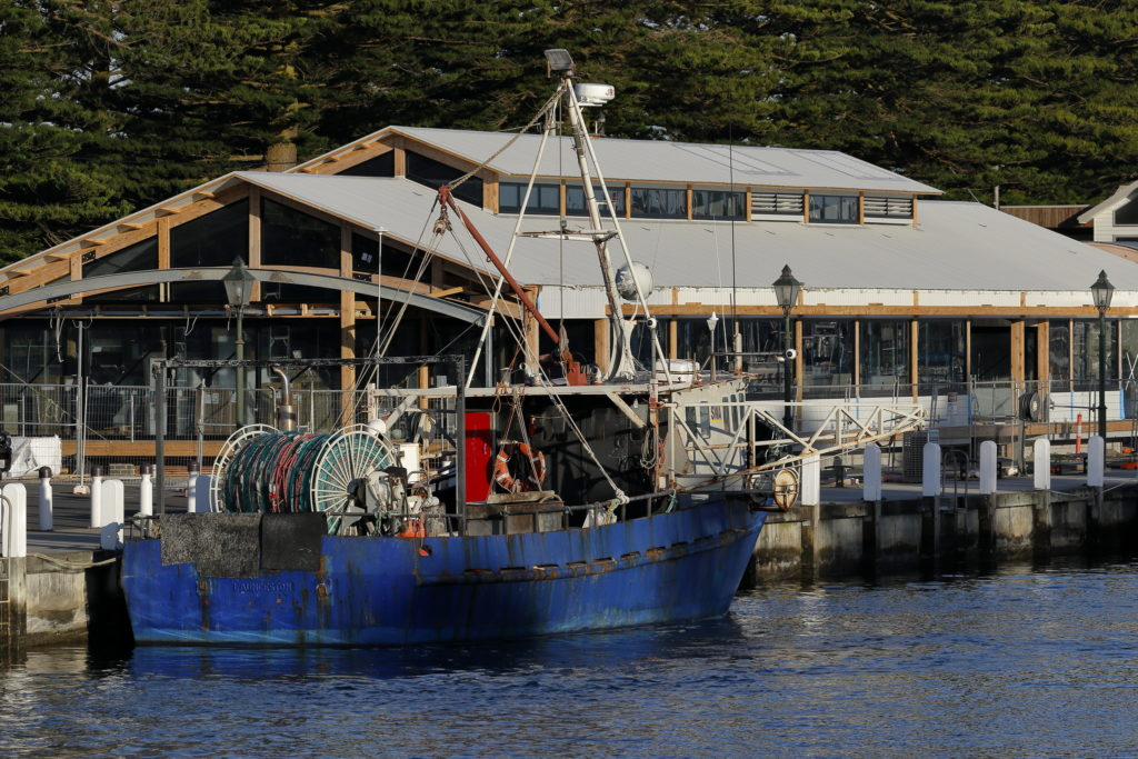 A blue fishing vessel (docked due to abalone disease) is berthed at a jetty with a large building on the wharf in the background.