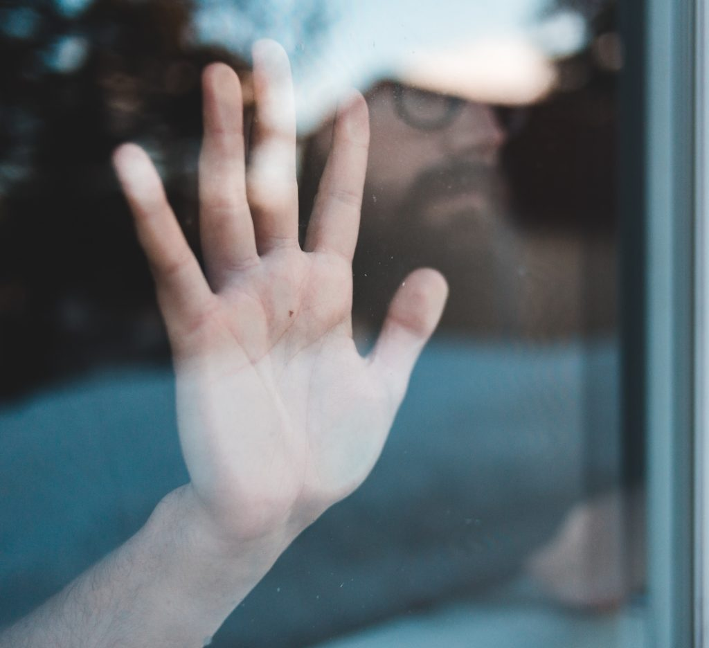 blurred image of man's face through closed window