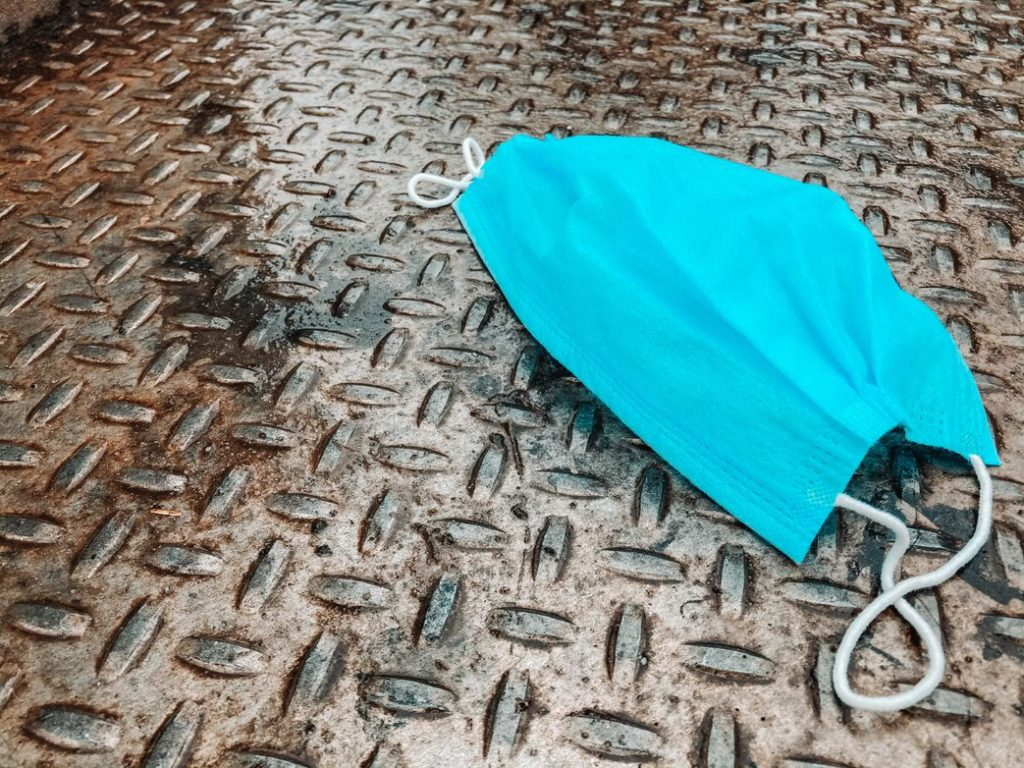 A blue facemask sits on a metal floor.