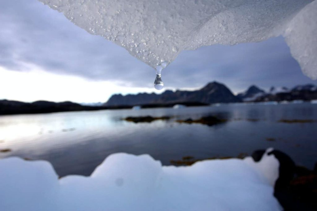 Image of a drop of water falling from ice with a body of water and snow in the background.