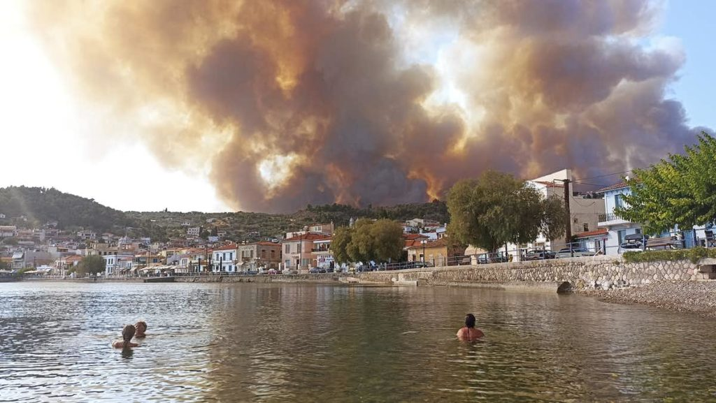 A photo of people in an ocean with a city on fire in the background.