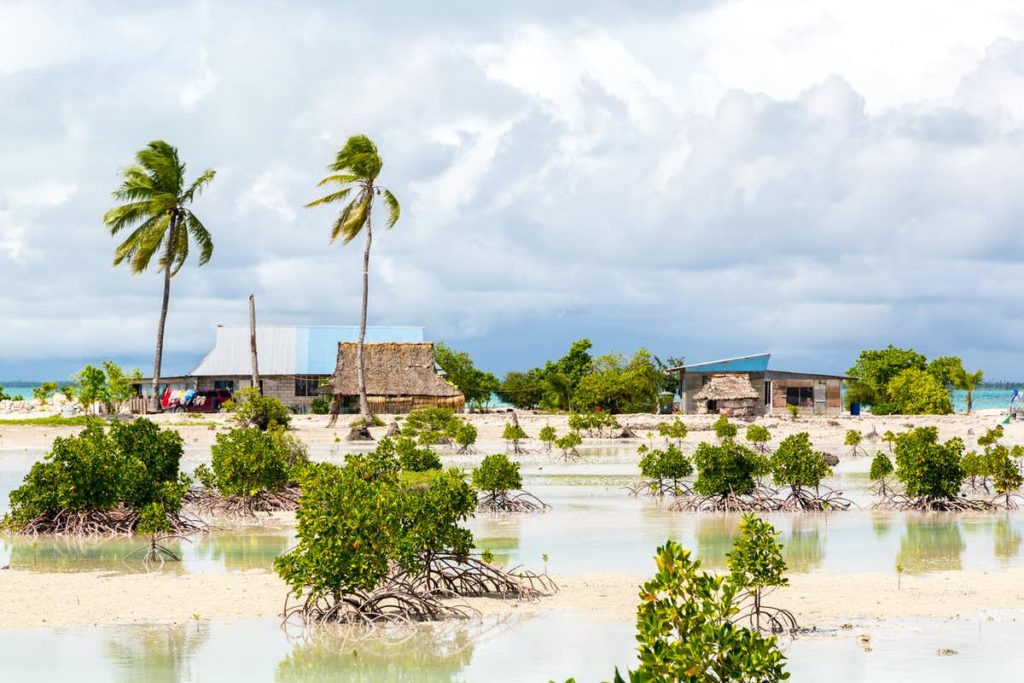 A photo of huts on a desert island surrounded by water.
