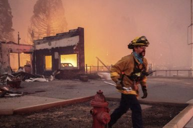 A photo of a firefighter walking through a burnt out environment.