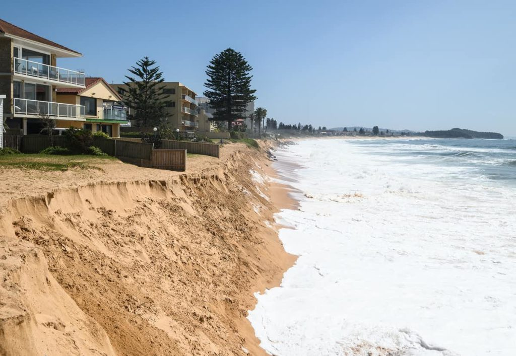 Photo of beachside homes where the ocean is very close to the homes and the sand is eroded.