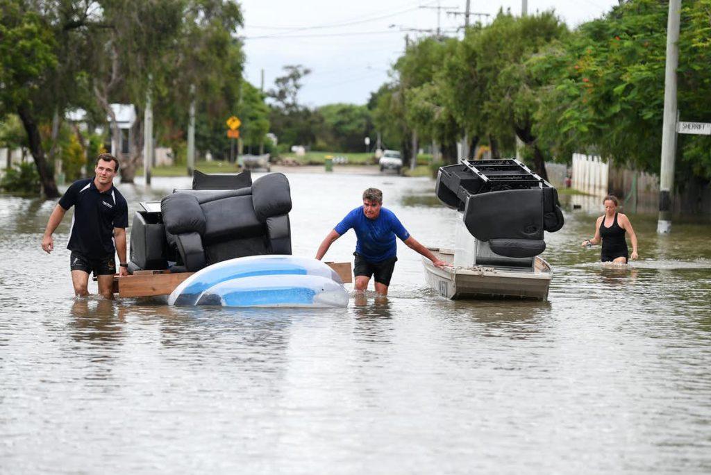 Men float furniture through floodwaters