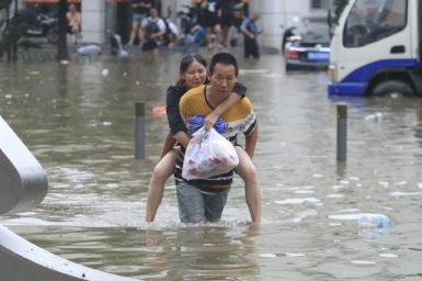 Image of people wading through a flood in a city.
