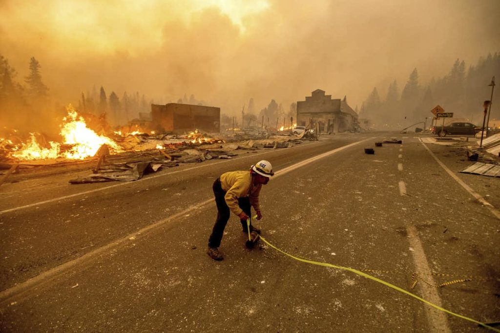 Image of a firefighter standing in a road with burning fires and buildings surrounding them.