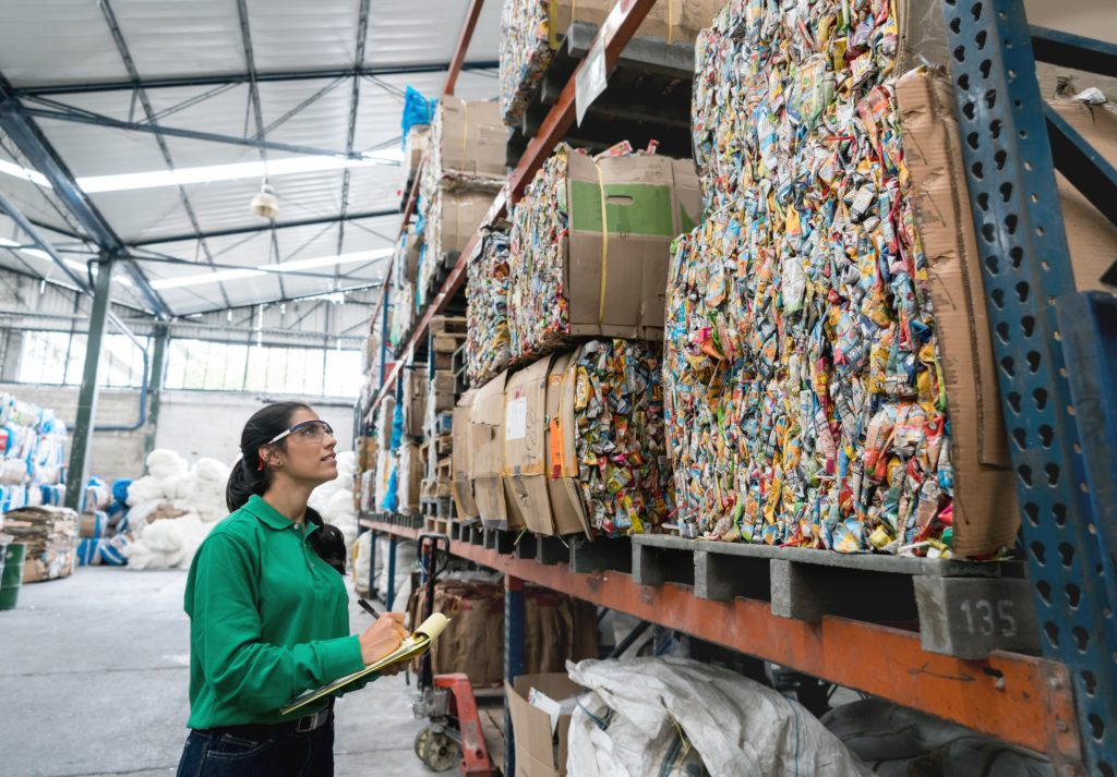 Portrait of a happy woman working in a recycling factory sorting the garbage and writing on a clipboard.