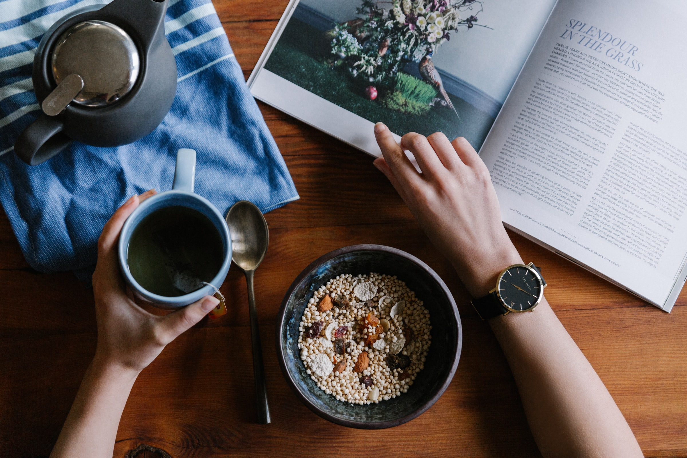 A person holding a coffee cup in their left hand and reading a magazine in their right hand. There is a bowl of cereal in the middle.