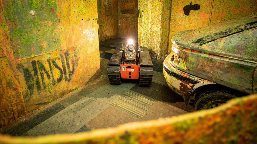 An orange robot in a tank like shape shines a light at the camera from a grungy warehouse floor.