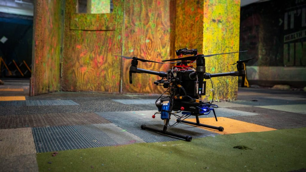 A drone sits on the mismatched carpeted floor of a grungy warehouse.