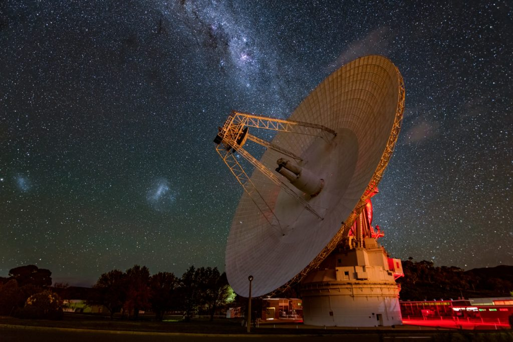 A satellite dish with stars in space in the background.