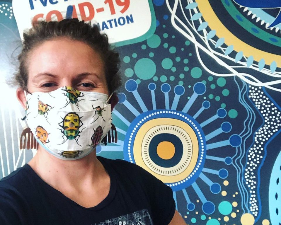 Woman with insect mask on smiling in CSIRO shirt. Showing of Music you can get vaccinated to