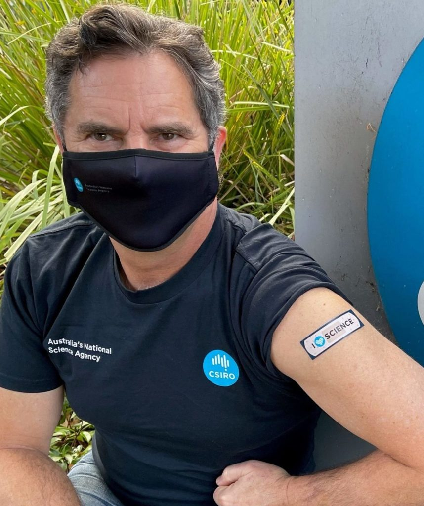 Man shows his arm and band-aid after vaccination.