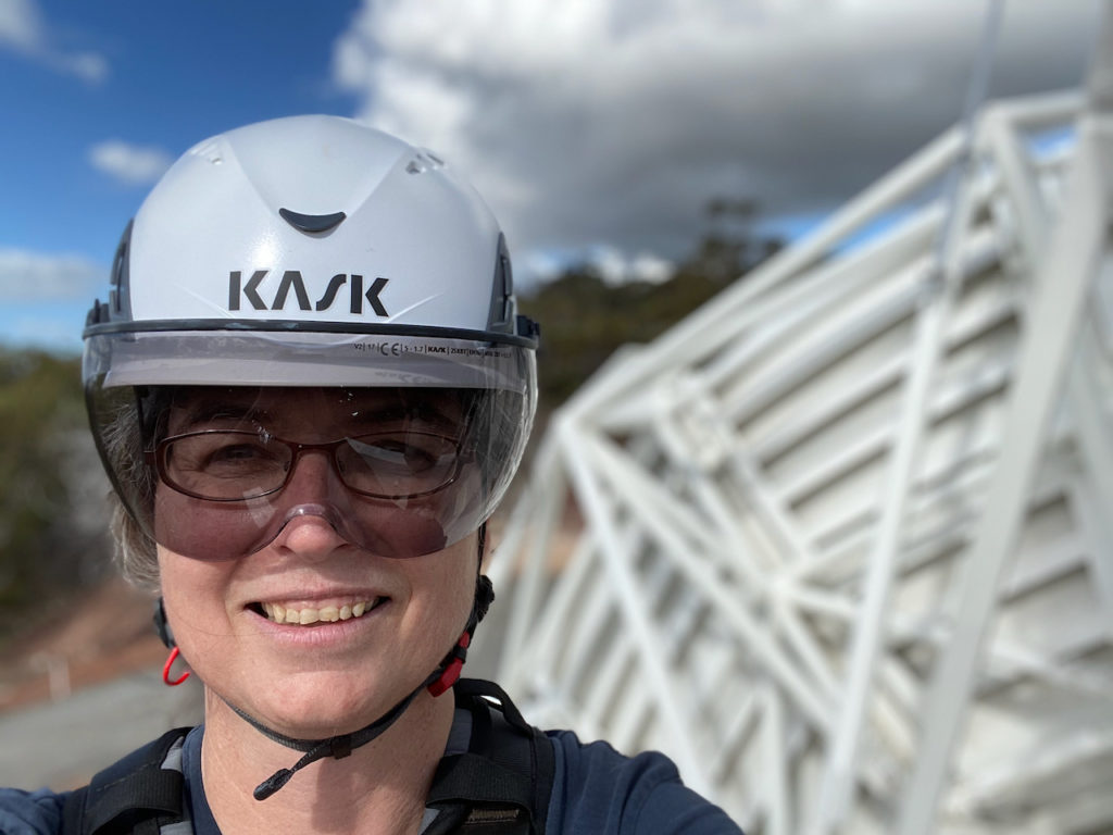 Photo of Suzy Jackson wearing a helmet, looking at the camera with a blue sky and machinery in the background.