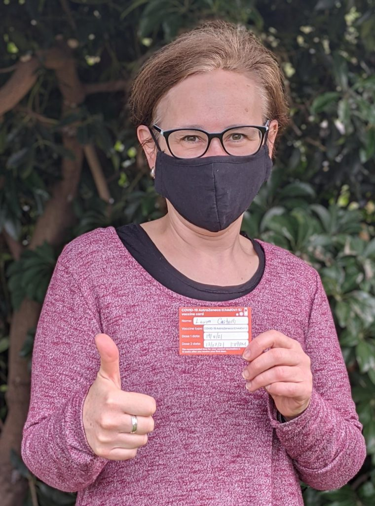 Woman wearing mask holds up her vaccine card and takes a vaccine selfie.