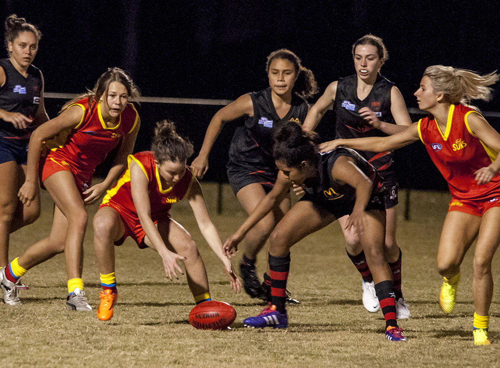 Young women playing Aussie Rules football. Traumatic brain injuries including concussion can occur in a range of sports.
