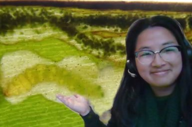 A woemn wearing glasses in front of a green background with a caterpillar in a leaf