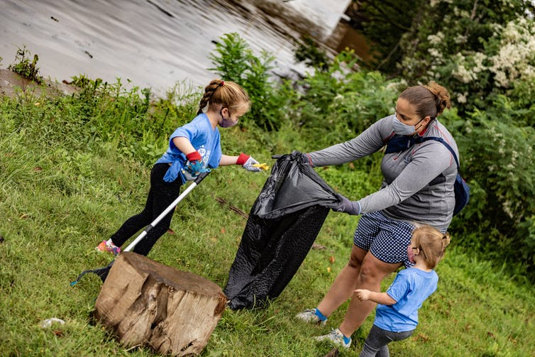 A woman wearing a mask holds up a garbage bag as children collecting rubbish outdoors place pieces inside the bag.