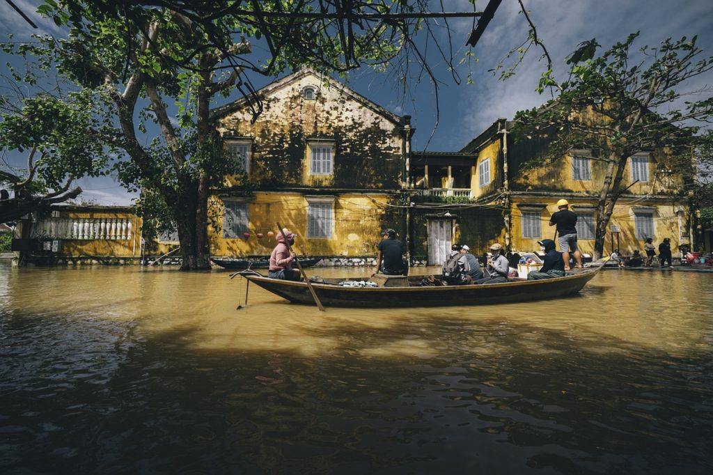 A Vietnam street flooded with brown water. People float in boats in front of yellow house facades.