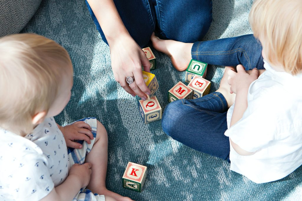 Lockdown tips for parents. Parent and two children playing with wooden alphabet blocks.